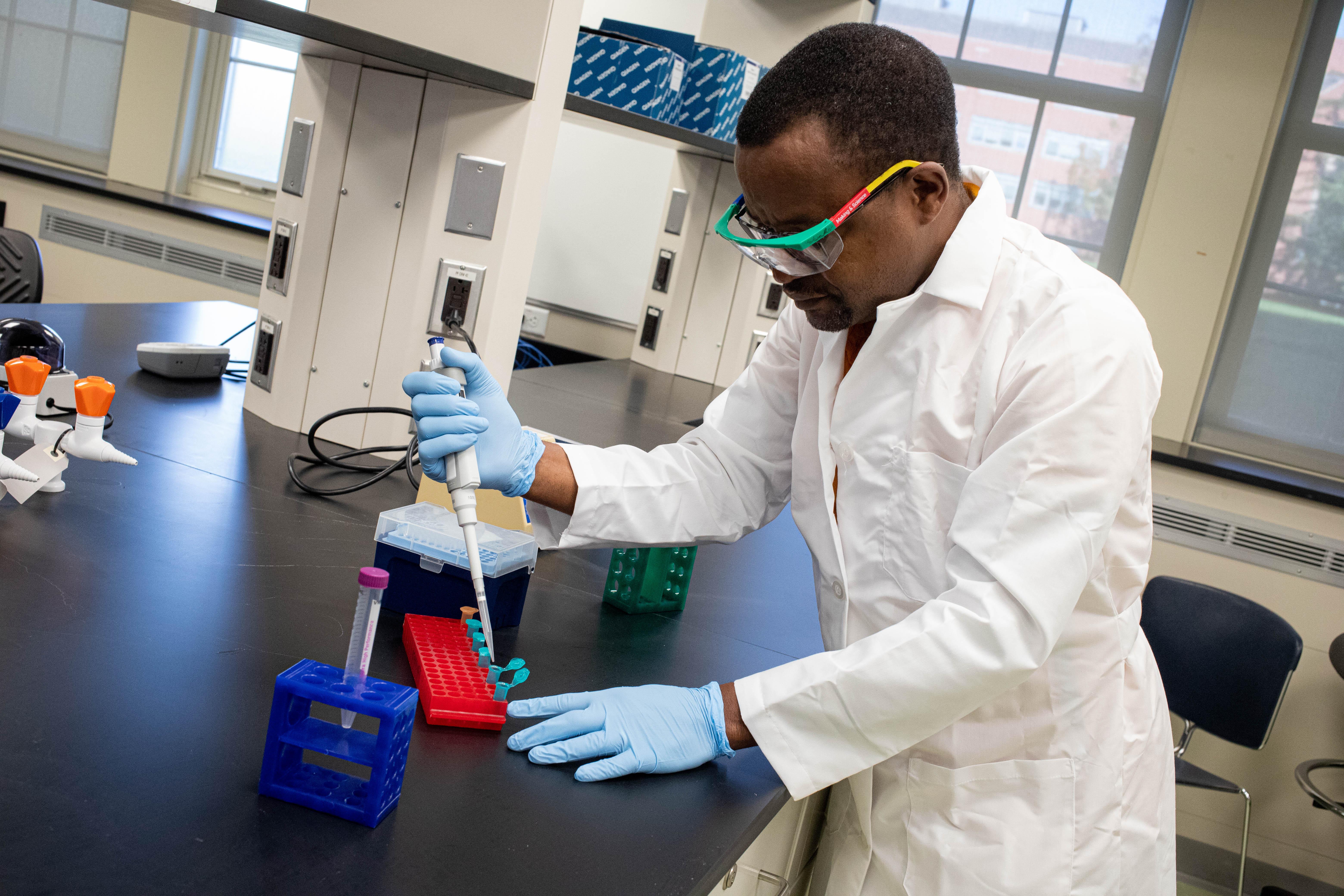 Man in lab coat performs lab work.